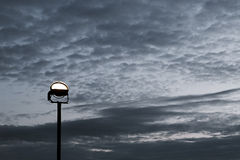 Reflector on the background of the cloudy sky Stock Image