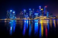 Reflejado en el agua las luces de la noche del centro de negocios en Singapur Imagenes de archivo