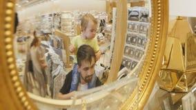 Reflejado en el padre Holds Girl del espejo de la tienda en hombros