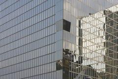 Reflejado en ventanas en el edificio de oficinas del rascacielos azul imagen de archivo