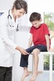 Reflejo de la rodilla de la prueba del neurólogo del niño foto de archivo libre de regalías