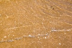 Reflejo de luz en la superficie del mar del movimiento en la playa de la arena Imagenes de archivo