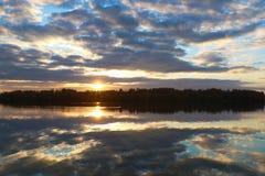 Reflektera av sjön när solnedgången med blå himmel fotografering för bildbyråer