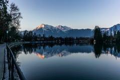 Reflektera för de Jungfrau och Eiger bergen i sjön av Thun FN Schweiz i bakgrunden tidigt på morgonen - 1 arkivfoto