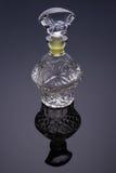 Reflekterade den crystal flaskan för snittexponeringsglas på bakgrund för blåa grå färger Arkivbild