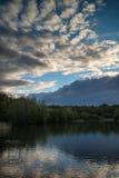 Reflekterade den vibrerande solnedgången för sommar i lugna sjövatten Royaltyfria Bilder