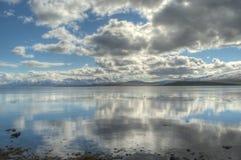Reflekterande fjord, blå himmel, moln och snöig berg i sommar Arkivbilder