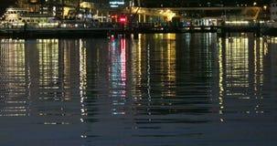 Reflekterande nattljus på en vattenyttersida stock video