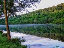 Reflekterande träd för Moselle flod av vattensolnedgången nära den Toul Frankrike tältplatsen Royaltyfri Foto