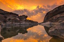 Reflekterande vatten för sten på solnedgången Arkivfoto