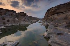 Reflekterande vatten för sten på solnedgången Royaltyfria Bilder
