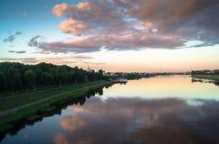 Reflekterar glansig yttersida för spegeln av Volgaet River dramatisk solnedgånghimmel Stad av Tver, Ryssland Royaltyfria Bilder