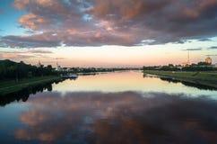 Reflekterar glansig yttersida för spegeln av Volgaet River dramatisk solnedgånghimmel Stad av Tver, Ryssland Arkivfoto