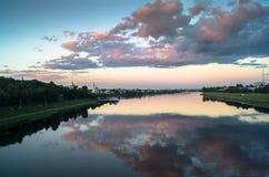 Reflekterar glansig yttersida för spegeln av Volgaet River dramatisk solnedgånghimmel Stad av Tver, Ryssland Royaltyfri Foto