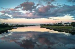 Reflekterar glansig yttersida för spegeln av Volgaet River dramatisk solnedgånghimmel Stad av Tver, Ryssland Royaltyfri Fotografi