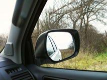 Reflekterat i en rearview I bakgrundsskoghösten Vinter bil Natur arkivfoton