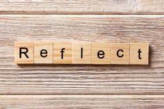 Reflektieren Sie das Wort, das auf hölzernen Block geschrieben wird Reflektieren Sie Text auf Tabelle, Konzept Stockfotografie