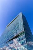 Reflektierende GlasBürogebäude gegen blauen Himmel mit Wolken und Sonne beleuchten Lizenzfreie Stockbilder