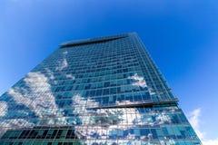 Reflektierende GlasBürogebäude gegen blauen Himmel mit Wolken und Sonne beleuchten Stockfoto