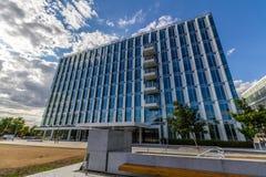 Reflektierende GlasBürogebäude gegen blauen Himmel mit Wolken und Sonne beleuchten Stockfotos