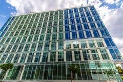 Reflektierende GlasBürogebäude gegen blauen Himmel mit Wolken und Sonne beleuchten Stockbild