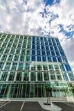 Reflektierende GlasBürogebäude gegen blauen Himmel mit Wolken und Sonne beleuchten Lizenzfreie Stockfotos