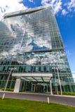 Reflektierende GlasBürogebäude gegen blauen Himmel mit Wolken und Sonne beleuchten Stockbilder