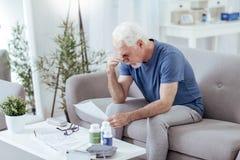 Reflektierender älterer Mann, der Anweisung nachforscht lizenzfreies stockbild
