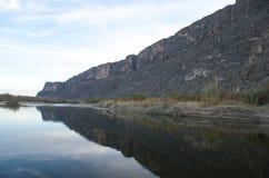 Reflektierender See überschattet durch einen großen Berg Lizenzfreies Stockbild