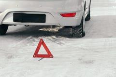 Reflektierendes Warndreieck vor Fahrzeug, eine Notsituation auf der Straße im Winter, ruft um Hilfe Auto aufgegliedert Lizenzfreie Stockfotos