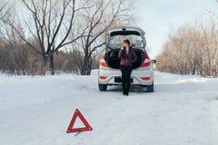 Reflektierendes Warndreieck vor Fahrzeug, eine Notsituation auf der Straße im Winter, ruft um Hilfe, Frauenunterhaltung lizenzfreies stockfoto