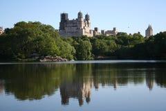 Reflektierte Gebäude, die Central Park übersehen Stockfoto