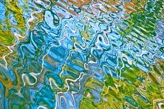 Reflexão abstrata bonita da água em cores azuis, amarelas e verdes imagem de stock royalty free