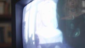 Reflexão colorida da menina na exposição velha da tevê que joga o vídeo dela no tempo real video estoque