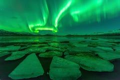 Reflexão da aurora boreal (aurora borealis) através de um lago em Islândia