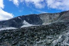 Reflexão da corrente de montanha em um lago pequeno no parque nacional de Jotunheimen em Noruega imagem de stock