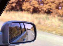 Reflexão da estrada ensolarada do outono no espelho do lado do carro imagem de stock royalty free