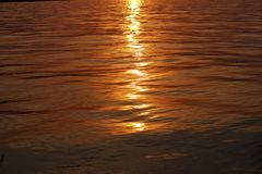 Reflexão da luz solar durante o por do sol na agua potável Imagens de Stock Royalty Free