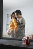 Reflexão da mulher gravida de abraço do homem Imagens de Stock