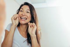 Reflexão da mulher que usa o fio dental imagem de stock royalty free