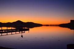 Reflexão da silhueta do cais do por do sol Fotografia de Stock