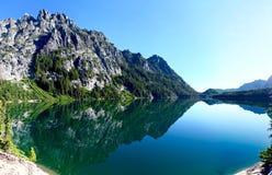 Reflexão das montanhas na água calma fotografia de stock
