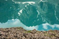 Reflexão das montanhas na água calma do lago Foto de Stock