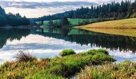 Reflexão das nuvens e da floresta no lago Zlatna, Eslováquia Fotografia de Stock