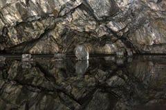 Reflexão das paredes da caverna em um lago subterrâneo congelado Foto de Stock