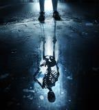 Reflexão de esqueleto na poça fotos de stock royalty free