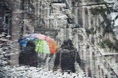 Reflexão de um par com um guarda-chuva do arco-íris Fotografia de Stock Royalty Free