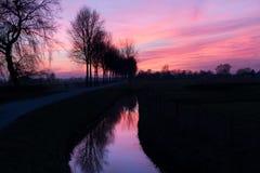 Reflexão de um por do sol cor-de-rosa em uma vala em uma área rural Imagem de Stock