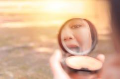 A reflexão de uma jovem senhora que põe sobre ela compõe Foto de Stock