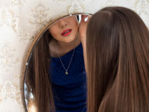 Reflexão de uma menina em um espelho que faça a composição Bordos vermelhos Foto de Stock Royalty Free